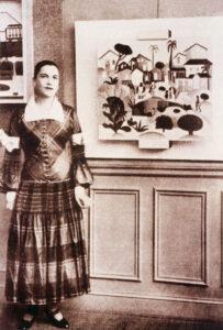 """Tarsila do Amaral con vestido del costurero Paul Poiret posa junto a su obra """"Morro de Favela"""" durante su exposición en París en 1926"""